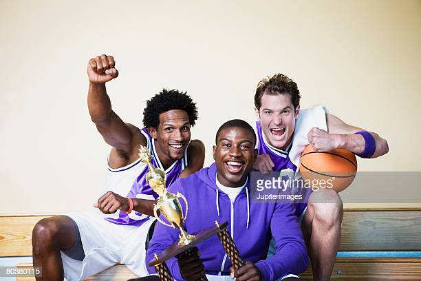 Cheering basketball players with trophy