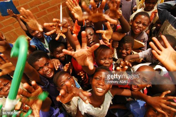 cheering black children waving their hands high angle view Lilongwe Malawi