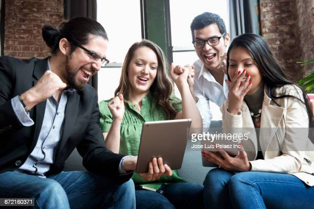 Cheering business people using digital tablets in office
