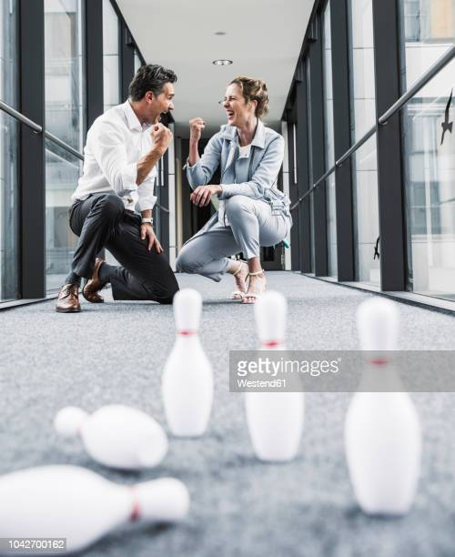cheering businessman and businessman in office passageway with fallen pins - stir crazy stock photos and pictures