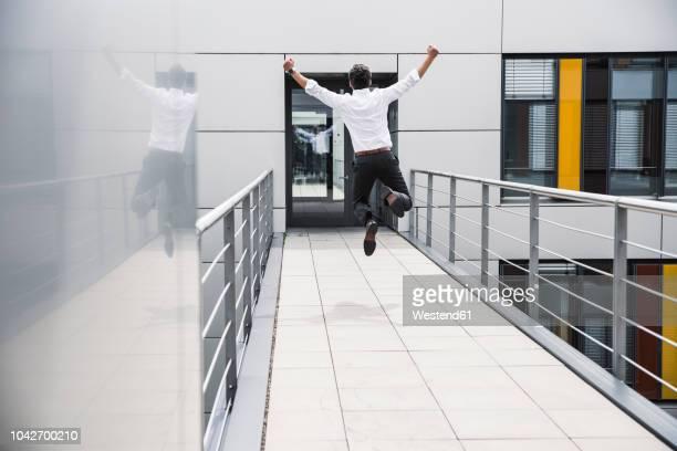 cheering businessman jumping on skywalk at office building - gewinnen stock-fotos und bilder