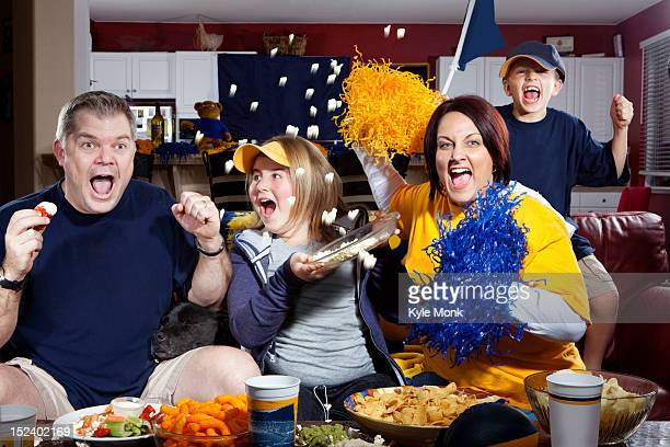 Cheering Caucasian family watching sports