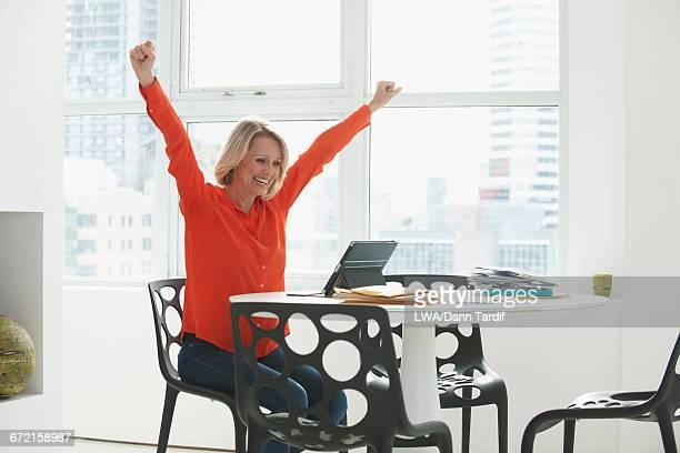 Cheering Caucasian woman using digital tablet at table