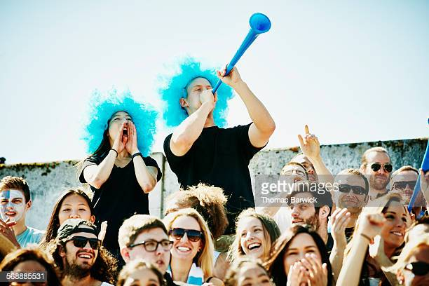 Cheering couple in wigs standing in crowd