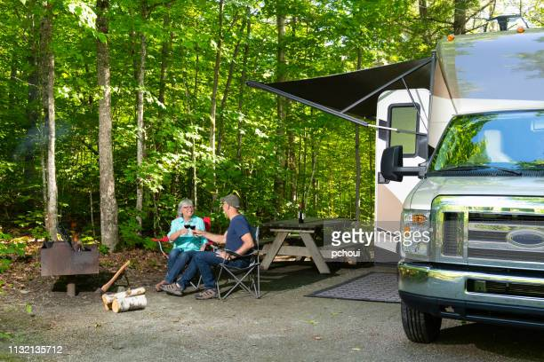 cheering couple near campfire - foldable stock pictures, royalty-free photos & images