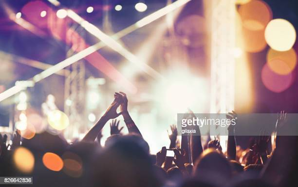 cheering crowd at a concert. - stage light stock pictures, royalty-free photos & images