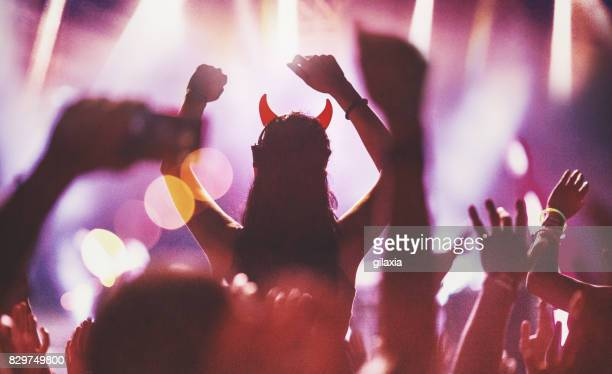 cheering crowd at a concert. - devil costume stock photos and pictures