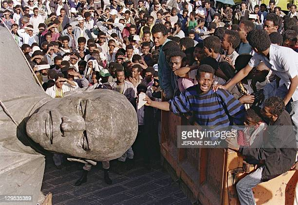 A cheering crowd of Ethiopian youths surrounds the toppled statue sculptured in a pure style of socialist realism of Russian Bolshevik revolutionary...