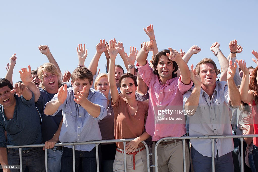 Cheering crowd with arms raised : Stock Photo
