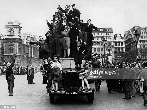 VE Day celebrations in London with cheering crowds and servicemen on the streets and hanging onto a truck 8th May 1945