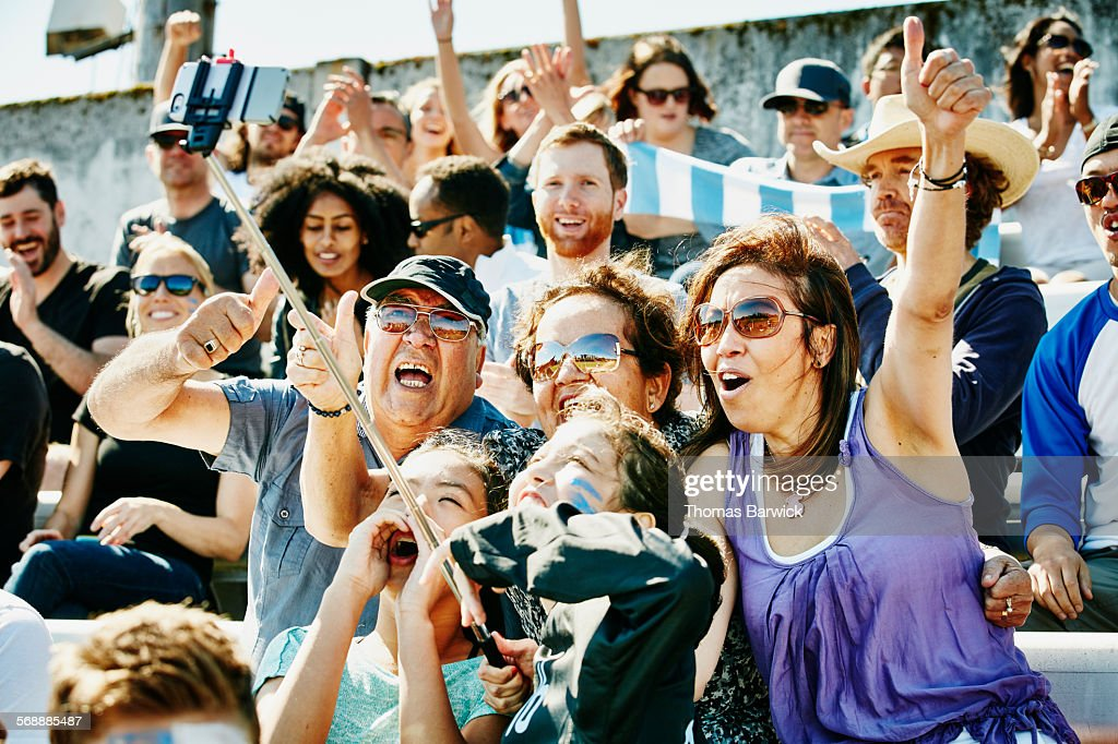 Cheering family at soccer match using selfie stick : Stock Photo