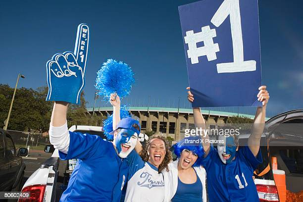 cheering fans holding sign - foam finger stock photos and pictures