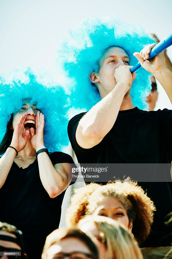 Cheering fans in wigs in crowd during soccer match : Stock Photo