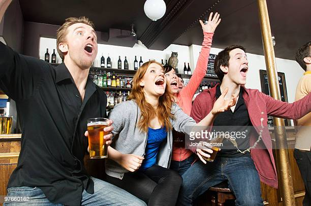 cheering fans watch sport on television in pub bar