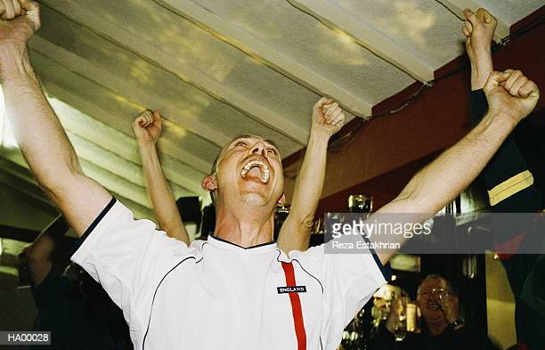 cheering football fan watching match in pub, arms raised, close-up - fan stock-fotos und bilder