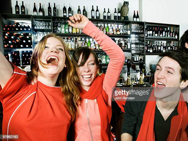 cheering football supporters celebrate in pub bar - supporter stock pictures, royalty-free photos & images