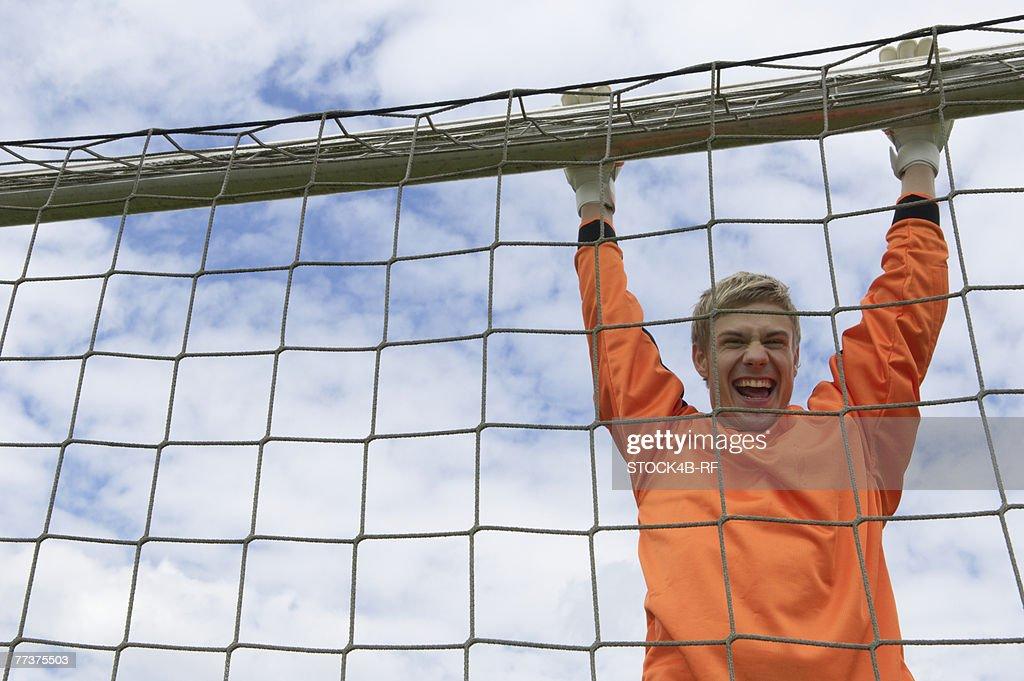 Cheering goalkeeper hanging on goal : Photo