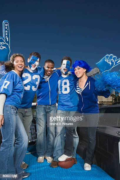 cheering group of football fans - foam finger stock photos and pictures