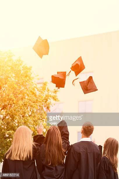 Jubeln Abiturienten werfen Kappen in die Luft.