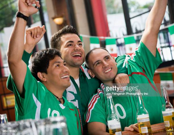 Cheering Hispanic men watching television in sports bar