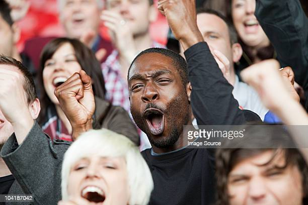 cheering man at football match - supporter stock pictures, royalty-free photos & images