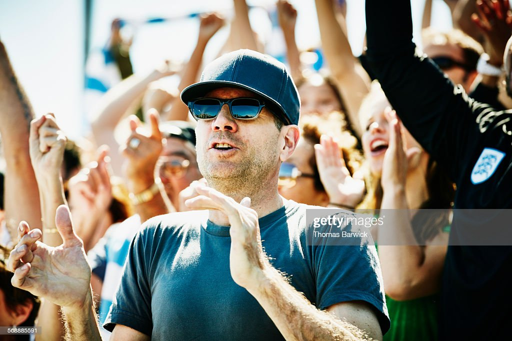 Cheering man in crowd at sports event in stadium : Stock Photo