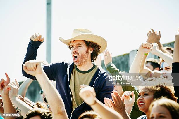 Cheering man standing in crowd during soccer match