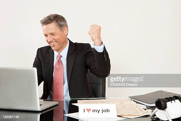Cheering manager at desk looking at laptop