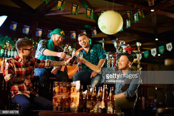 cheering men toasting with beer glasses - st patricks day stock pictures, royalty-free photos & images