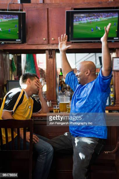 cheering men watching television in sports bar - rivalidade - fotografias e filmes do acervo