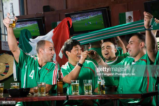 Cheering men watching television in sports bar