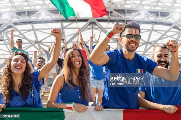 cheering multi-ethnic game supporters - ita foto e immagini stock