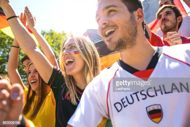 cheering multi-ethnic game supporters - germany stock pictures, royalty-free photos & images