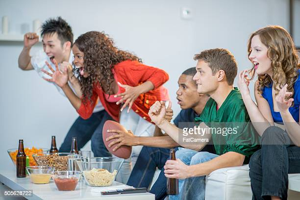 cheering on their football team during the superbowl - american football sport stock photos and pictures