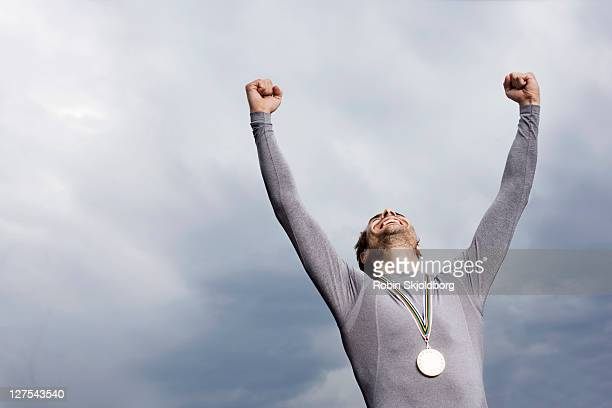 cheering runner wearing medal - medalist stock pictures, royalty-free photos & images