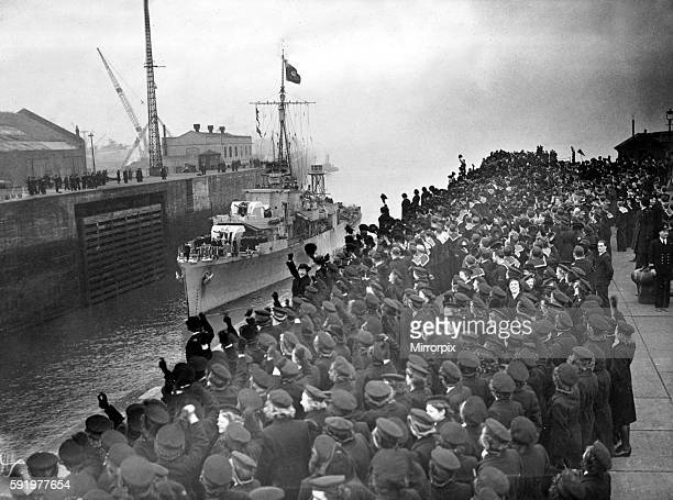 Cheering sailors and Wrens of the Royal Navy line the entrance to Gladstone dock in Bootle, Liverpool to celebrate the arrival of the U-boat...