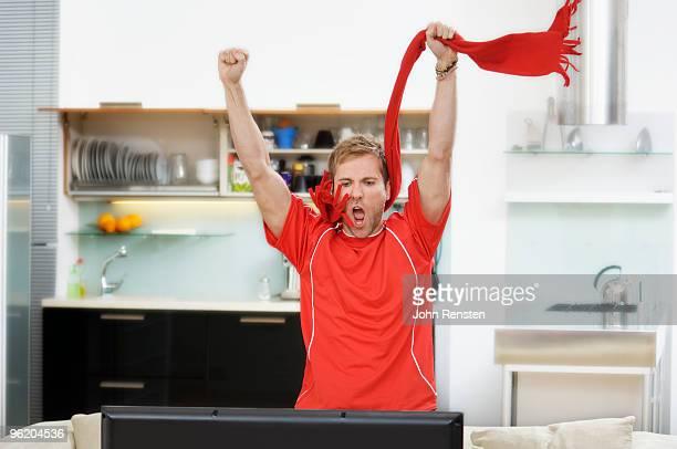 cheering sport fan shouting at television