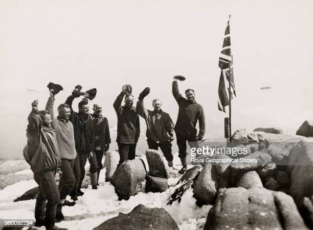Cheering the flag on the summit of Proclamation Island 13th January 1930 the ship is faintly outlined in the distance some 800 feet below Harold...