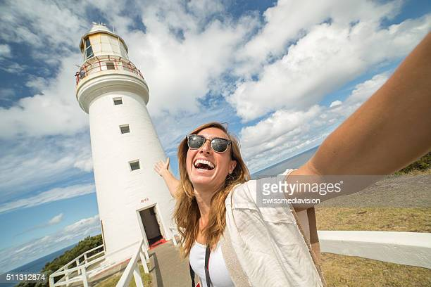 Cheering tourist woman takes selfie portrait with Cape Otway lighthouse