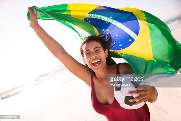 Cheering woman football fan with brazilian flag