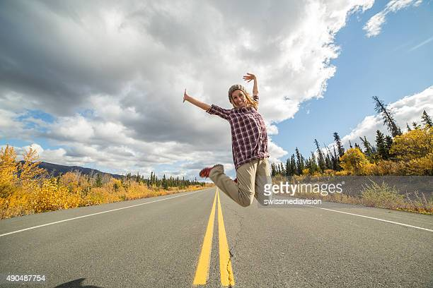 Cheering woman jumping high up on road