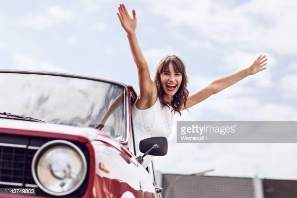 cheering woman looking out of vintage car - ausgestreckte arme stock-fotos und bilder