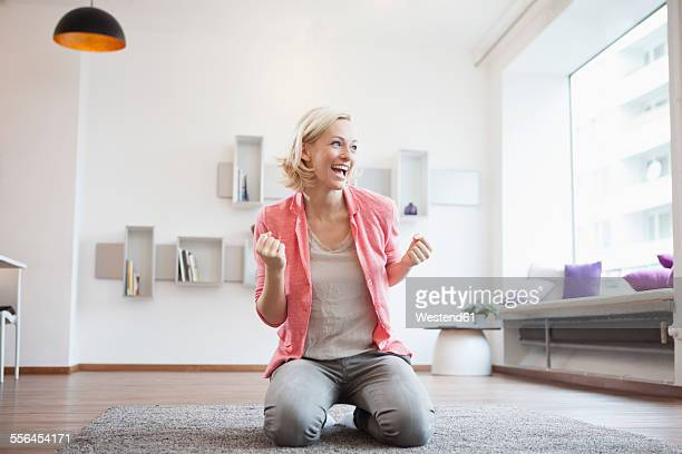 Cheering woman sitting on carpet at living room