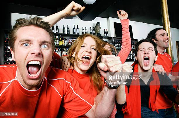 cheering world cup fans celebrate in pub bar - supporter stock pictures, royalty-free photos & images