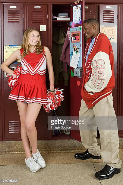 cheerleader and baseball player by lockers - black cheerleaders stock photos and pictures