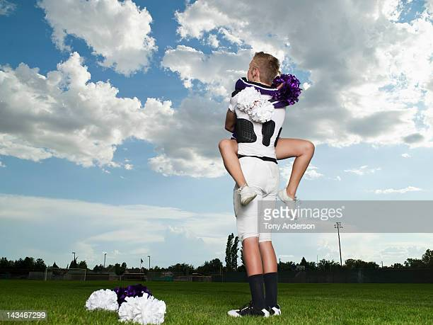 cheerleader and footballer hugging - candid cheerleaders stock photos and pictures