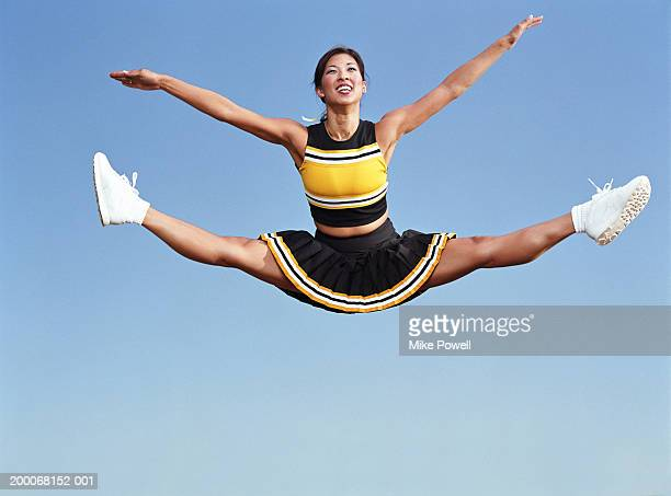 cheerleader doing splits in mid air - asian cheerleaders stock photos and pictures