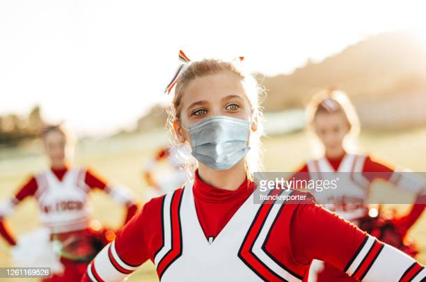 cheerleader doing sport with face mask - cheerleader stock pictures, royalty-free photos & images