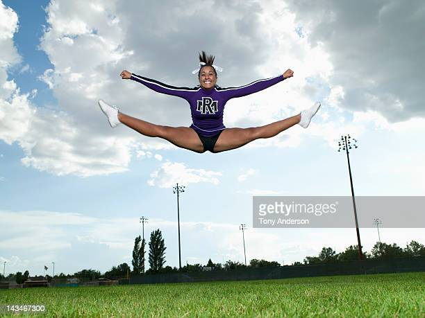 cheerleader doing toe touch jump - black cheerleaders stock photos and pictures