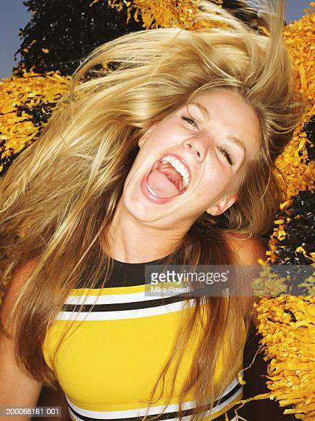 cheerleader flipping hair, laughing, surrounded by pompoms, portrait - girls open mouth stockfoto's en -beelden